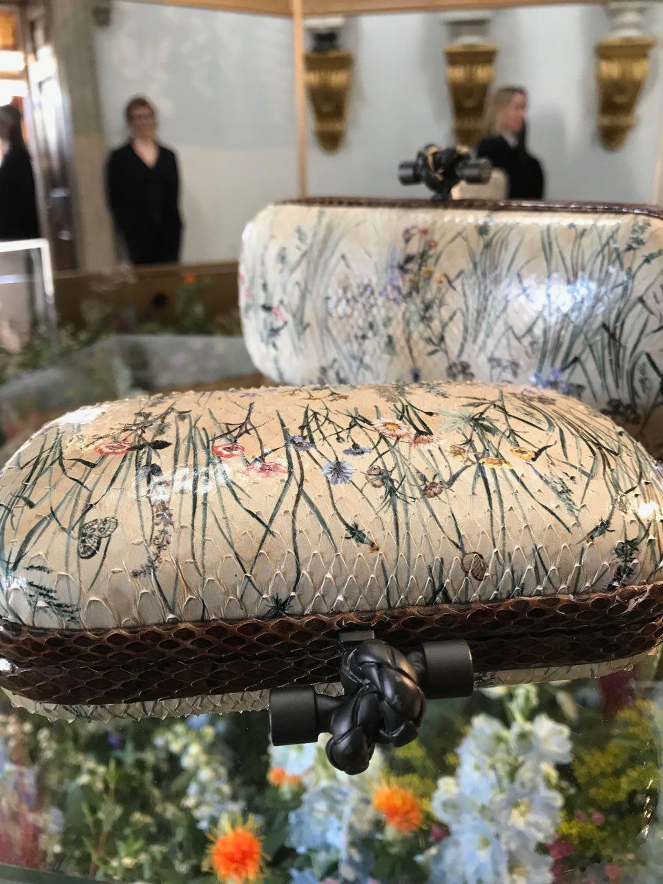 Hand painted Bottega Veneta snakeskin clutch bag, displayed above fresh flowers