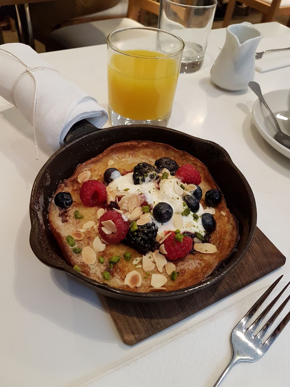 Dutch baby pancake with poached plums and Iranian pistachios served with orange yoghurt and mixed berries.