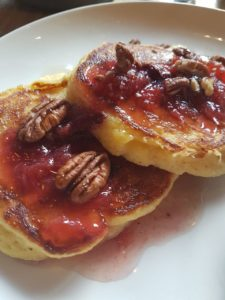 Ricotta polenta hotcakes with stewed plums, maple yogurt cream and pecans at Caravan